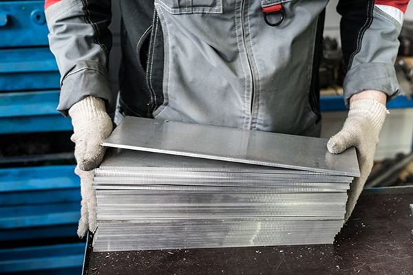 Image of steel plates held by industrial worker.